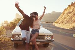 Retrato de los pares jovenes que se colocan al lado del coche clásico imagen de archivo