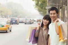 Retrato de los pares jovenes sonrientes que llevan bolsos de compras coloridos y que esperan el autobús en la parada de autobús, P Fotos de archivo libres de regalías