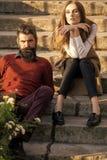 Retrato de los pares de la moda Pares que se sientan en las escaleras al aire libre Fotografía de archivo