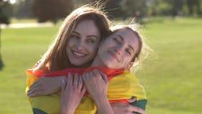Retrato de los pares lesbianos alegres que abrazan en parque almacen de metraje de vídeo
