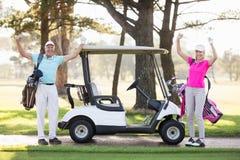 Retrato de los pares maduros sonrientes del golfista con los brazos aumentados Foto de archivo