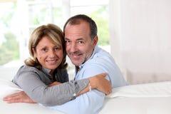 Retrato de los pares mayores felices que se sientan en el sofá y el abarcamiento Imágenes de archivo libres de regalías