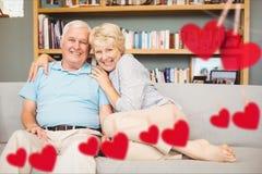 Retrato de los pares mayores que abrazan en el sofá Imágenes de archivo libres de regalías