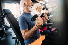 Retrato de los pares mayores que ejercitan en gimnasio imagen de archivo libre de regalías