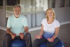 Retrato de los pares mayores que se sientan en bolas de la aptitud con pesas de gimnasia Imágenes de archivo libres de regalías