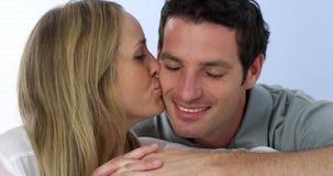 Retrato de los pares que mienten en besarse del sofá Foto de archivo