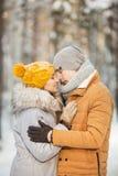 Retrato de los pares que se besan de los jóvenes en un color gris y anaranjado de la ropa en un invierno Imágenes de archivo libres de regalías