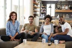Retrato de los pares que se sientan en hablar de Sofa With Friends At Home Imágenes de archivo libres de regalías