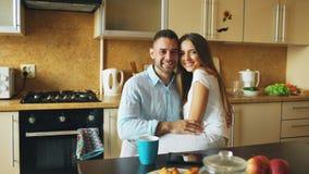Retrato de los pares sonrientes felices sittting en la madrugada de la cocina en casa imagen de archivo libre de regalías