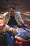 Retrato de los pares sonrientes que descansan sobre campo en la granja Imagenes de archivo