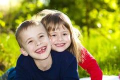 Retrato de los pequeños niños sonrientes felices muchacho y muchacha en soleado Imagen de archivo libre de regalías