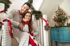 Retrato de los pijamas que llevan de los pares que se sientan en las escaleras el mañana de la Navidad fotografía de archivo libre de regalías