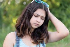 Retrato de los problemas ocupados de la muchacha adolescente en naturaleza del verano Fotografía de archivo libre de regalías