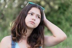Retrato de los problemas ocupados de la muchacha adolescente en naturaleza del verano Foto de archivo