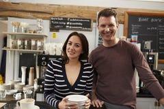 Retrato de los propietarios de negocio que trabajan detrás de contador en el café imagen de archivo