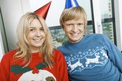 Retrato de los suéteres de la Navidad de los pares y de los sombreros sonrientes del partido que llevan en sala de estar en casa Fotos de archivo libres de regalías