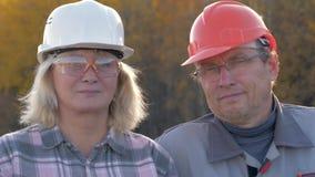 Retrato de los trabajadores de construcción un hombre y una mujer en un casco que mira la cámara metrajes