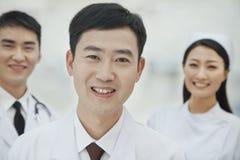 Retrato de los trabajadores sonrientes de la atención sanitaria en China, de dos doctores y de la enfermera en el hospital, mirand Imagenes de archivo