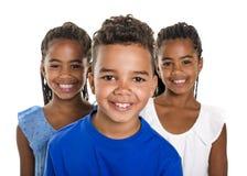 Retrato de los tres niños negros felices, fondo blanco imagenes de archivo