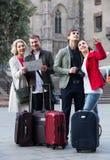 Retrato de los turistas con el mapa y el equipaje que ven las vistas en E Imágenes de archivo libres de regalías