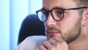 Retrato de los vidrios que llevan barbudos de un hombre joven que se sientan en su oficina que trabaja en un ordenador La pantall almacen de metraje de vídeo