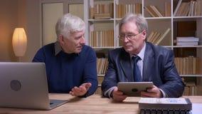 Retrato de los viejos hombres de negocios que trabajan as? como el ordenador port?til y la tableta que discuten activamente el pr almacen de video