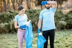 Retrato de los voluntarios con los bolsos de los desperdicios en el parque fotos de archivo libres de regalías