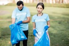 Retrato de los voluntarios con los bolsos de los desperdicios en el parque imágenes de archivo libres de regalías