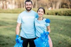 Retrato de los voluntarios con los bolsos de los desperdicios en el parque foto de archivo