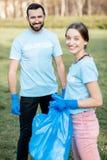 Retrato de los voluntarios con los bolsos de los desperdicios en el parque imagen de archivo libre de regalías