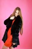 Retrato de louro novo encantador em um casaco de pele preto Foto de Stock