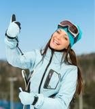 Retrato de medio cuerpo del esquiador en declive de la hembra que manosea con los dedos para arriba Foto de archivo libre de regalías
