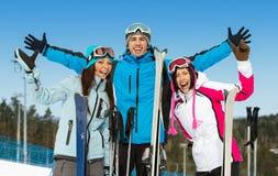 Retrato de medio cuerpo del grupo de amigos alpinos del esquiador con las manos para arriba Imágenes de archivo libres de regalías