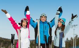 Retrato de medio cuerpo del grupo de amigos del esquiador de las montañas con las manos para arriba Fotos de archivo
