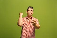 Retrato de medio cuerpo masculino hermoso aislado en backgroud verde del estudio El hombre sorprendido emocional joven Foto de archivo libre de regalías