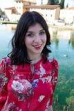 Retrato de medio cuerpo muy de una sonrisa, muchacha negra de pelo largo que mira en la cámara fotos de archivo