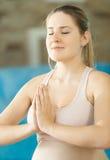 Retrato de meditar a la mujer sonriente joven foto de archivo libre de regalías