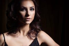 Retrato de meninas 'sexy' bonitas nas sombras em um vestido preto no estúdio em um fundo preto Imagem de Stock Royalty Free