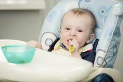 Retrato de 9 meses adoráveis do menino idoso que come no cadeirão no jogo Foto de Stock Royalty Free