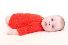 Retrato de 2 meses de bebé en mono rojo Imagen de archivo libre de regalías