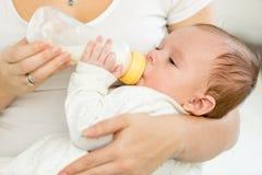 Retrato de 3 meses del bebé que come la leche de la botella Fotos de archivo libres de regalías