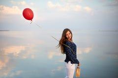 Retrato de Minimalistic de la mujer joven con el balón de aire rojo y del actual bolso cerca de la orilla del mar tranquilo o del Imagen de archivo libre de regalías