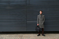 Retrato de moda del líder o del funcionario del hombre de negocios con la cartera en su mano contra la perspectiva de moderno imagen de archivo libre de regalías