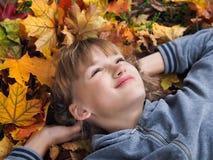 Retrato de muchachas hermosas felices entre las hojas de otoño Imagen de archivo libre de regalías
