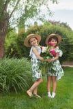 Retrato de muchachas hermosas sonrientes con el ramo de peonías contra hierba verde en el parque del verano Foto de archivo libre de regalías