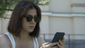 Retrato de mujer tendida sobre hierba verde en el parque de la ciudad y usando teléfono móvil. Mujer joven descansando sobre la  metrajes