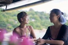 Retrato de 2 mujeres asiáticas que charlan, bebiendo y sonriendo en la barra de la playa en verano foto de archivo libre de regalías