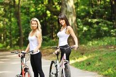 Retrato de mujeres bastante jovenes con la bicicleta en un parque Fotos de archivo libres de regalías