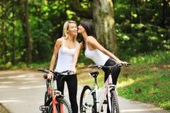 Retrato de mujeres bastante jovenes con la bicicleta en un parque Imagen de archivo libre de regalías