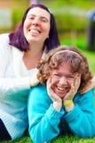 Retrato de mujeres felices con incapacidad en césped de la primavera Foto de archivo libre de regalías